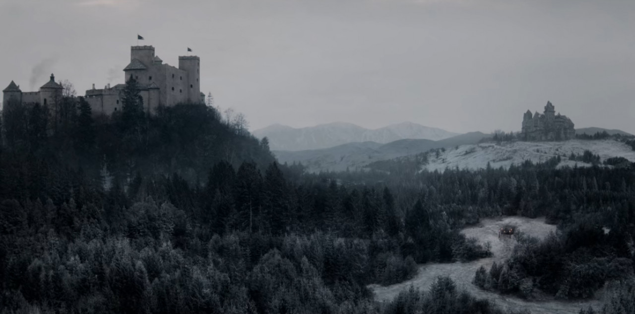 This screenshot from The Witcher shows Vizima Castle on the left. In the background is Old Vizima Castle which has been abandoned and left to fall into disrepair (Austria's Kreuzenstein Castle in real life).