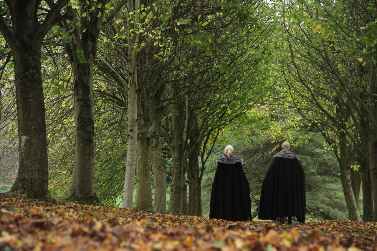 Fans in costume stroll through the Lime Tree Tunnel Walk at Winterfell