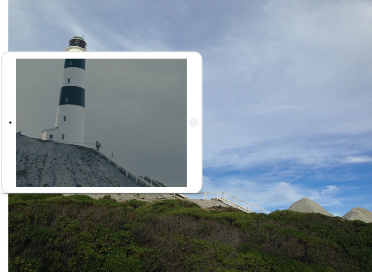 Tom carries Isabel down the steep wooden steps at the foot of the lighthouse.