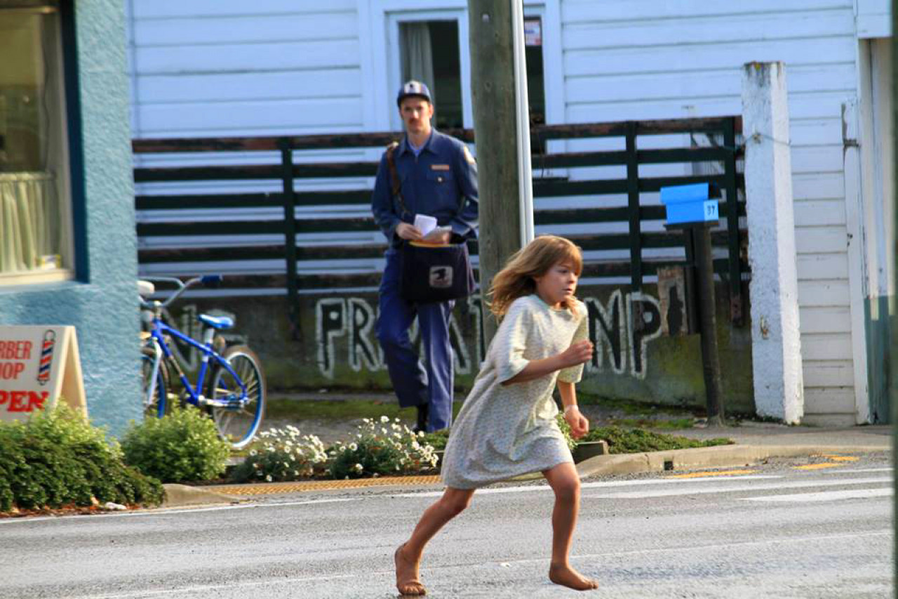 Pete (Oakes Fegley) running up the main street of Tapanui/Millhaven.