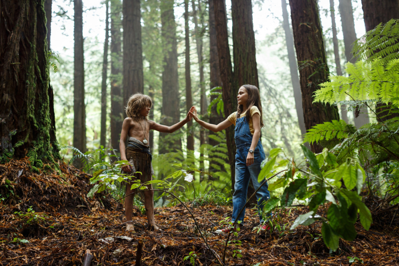 A scene from Pete's Dragon: Wild child Pete, who lives in the woods with his Dragon friend Elliot, meets Natalie from the nearby town of Millhaven.