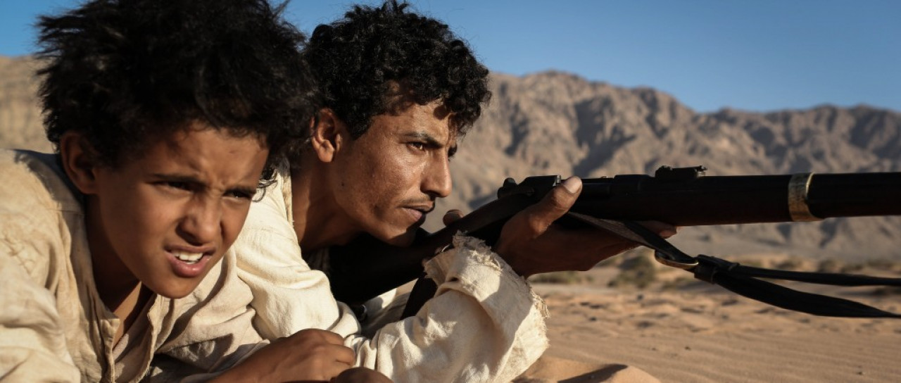 Huseen (right) stars as the brother of the main character - eight-year old Theeb (Jacir Eid, left). In this scene at the beginning of the movie, Huseen teaches Theeb how to use a rifle.